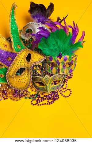 A festive colorful group of mardi gras or carnivale mask on a yellow background. Venetian masks.