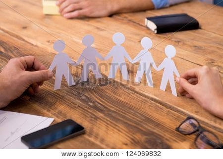 Close up of hands of man and woman holding paper people chain. Businesspeople holding paper man chain depicting solidarity and friendship. Closeup of symbol of unity and strength and togetherness.