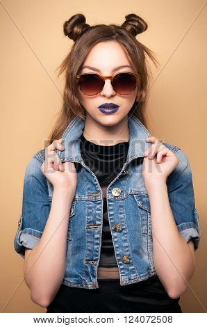 Beautiful young woman in sunglasses. Spring-summer outfit. Hairstyle Coachella. Denim Jacket, dark lipstick. Cute Chinese, Asian-Caucasian woman, fashionable . Yellow background. Toned image. poster
