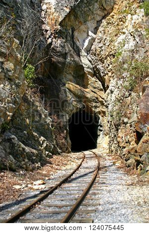 railroad tracks bend into a tunnel carved in sandstone