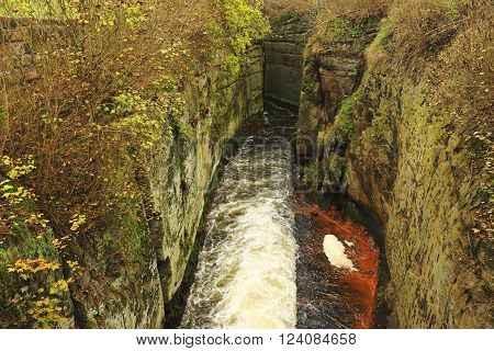 Water of small river flow at historical wooden weir. Terrible smell water with bubbles and reflection. Stony walls of weir
