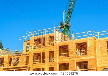 Your dream home. New residential construction house framing and green crane.