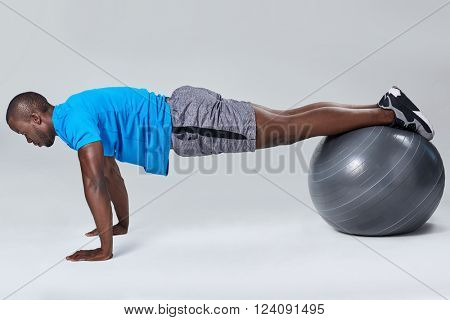 Fit healthy man uses pilates gym ball as part of toning and muscle building training exercises