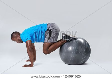 Fit healthy man uses pilates gym ball as part of toning and muscle core building training exercises