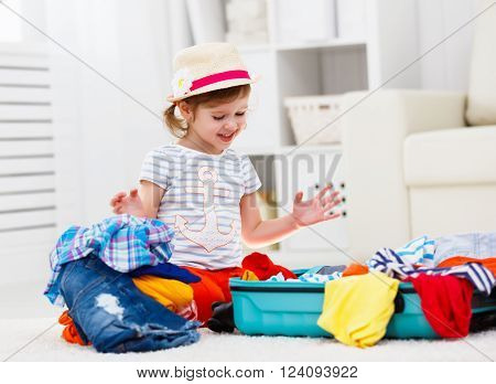 happy child girl tourist packs clothes into a suitcase for travel vacation