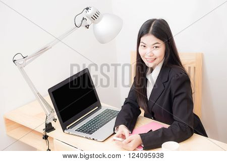 Portrait Of Happy Asian Businesswoman  Sitting At Her Workplace