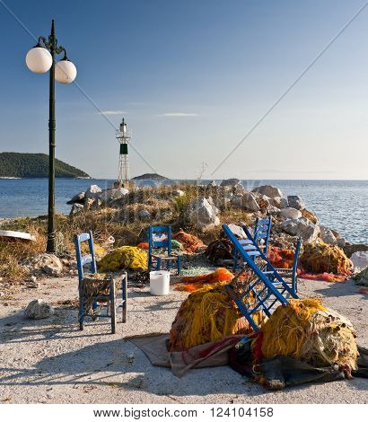 Multicolored fishing nets and blue chairs on the pier street lantern and small lighthouse next to the sea Skopelos island; Sporades; Greece