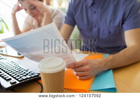business, startup, fail, crisis and people concept - close up of creative team with papers in office