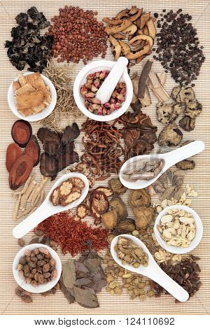 Chinese herb selection used in traditional alternative herbal medicine in porcelain mortar and pestle, bowls and spoons over bamboo background.