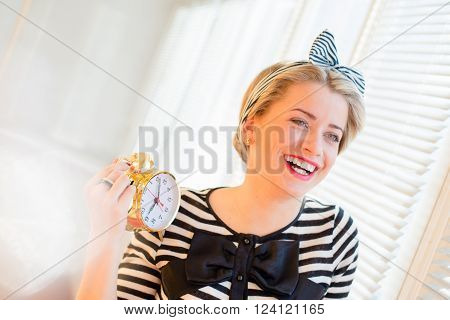 Portrait of a beautiful happy smiling young pinup woman showing alarm clock standing by the bright sunny window poster