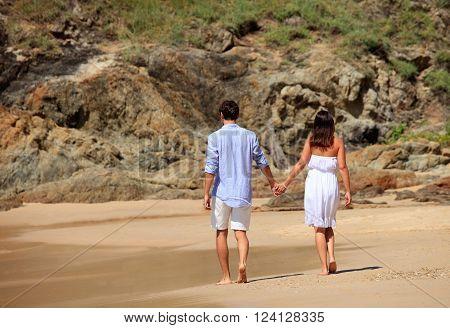 Cheerful couple walking on beach on rock background
