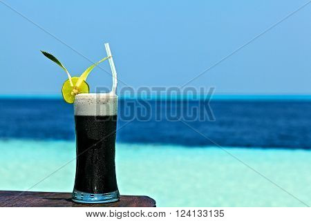 Glass of the black drink is on a beach table (Maldives, The Indian Ocean)