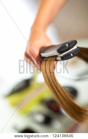 Close-up of a hairdresser straightening long blonde hair with hair irons. ** Note: Visible grain at 100%, best at smaller sizes