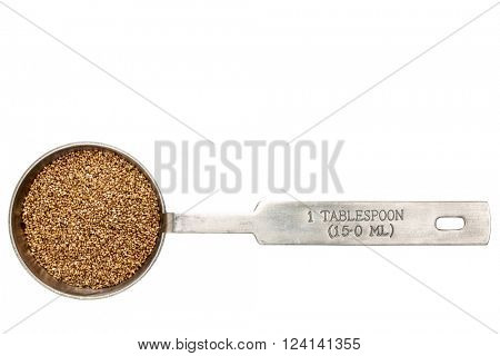 gluten free teff grain  in a metal measuring tablespoon isolated on white