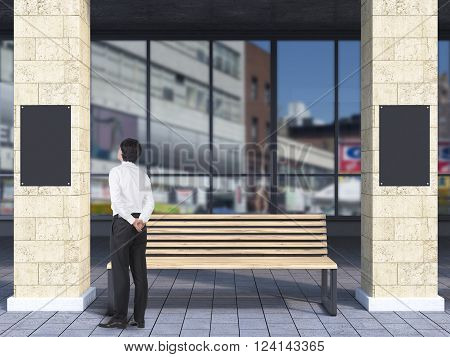 Businessman near bench under portico between columns looking at black poster. Concept of waiting at bus stop.