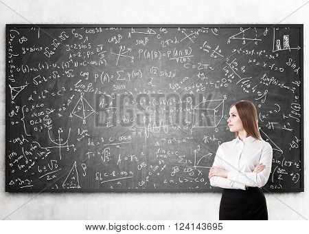Young girl with hands crossed standing at blackboard many formulas and geometry sketches on it. Concept of education.