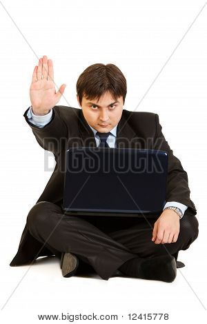 Sitting on floor with laptop serious businessman showing stop gesture isolated on white