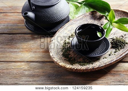 Green tea with black utensils on wooden table