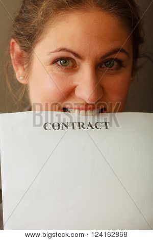 Contracts and agreements concept. Middle aged smiling business woman biting contract agreement. Face emotion expression.