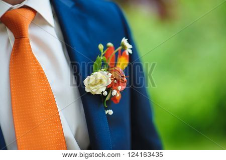 wedding beautiful boutonniere on suit of groom. Man in blue suit shirt and orange tie.