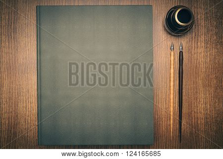 Closed green book, ink-pot and two pens on wooden desktop. Mock up, 3D Render