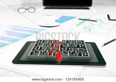 Tablet with maze placed on business charts and graphs. 3D Rendering