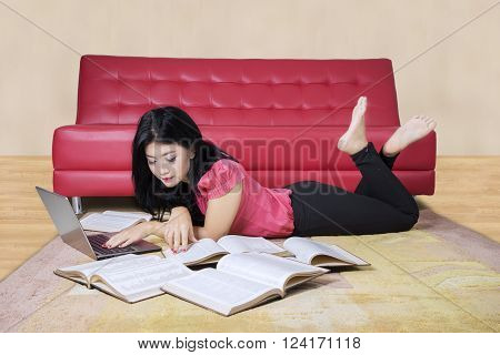 Picture of a pretty female student doing homework with a laptop and book on the carpet at home