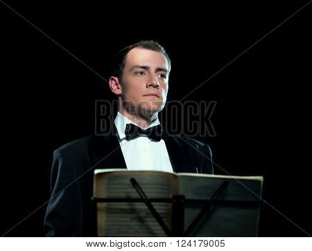 Studio portrait of young man conducts the orchestra poster