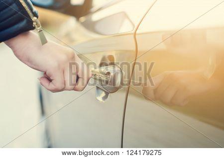 Woman with car key. Opening car door. Woman´s hand unlocking a door on a car. Sunlight. Transportation.