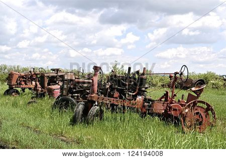 Old tractors with parts missing are lined up in a junkyards and used for salvage and scrap metal.