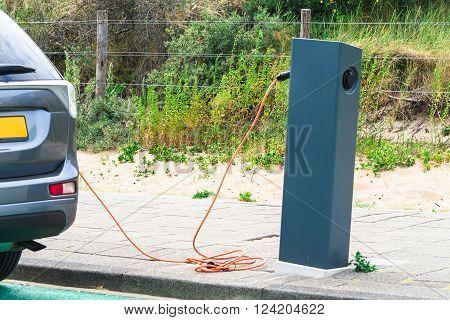 DEN HAAG, SCHEVENINGEN, THE NETHERLANDS - JUNE 17, 2015: Electric car at a charging station on the beach parking in Scheveningen Holland. Seperate parking with charging station for electric vehicles.