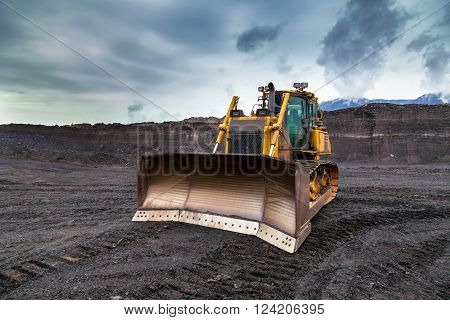 The bulldozer working in coal mines and cloudy sky