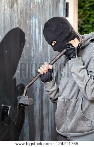 a burglar breaking open of a padlock metal door poster