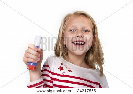 sweet beautiful female child 6 to 8 years old with cute blonde hair and blue eyes holding glue stick isolated on white background in education and primary or junior school supplies concept