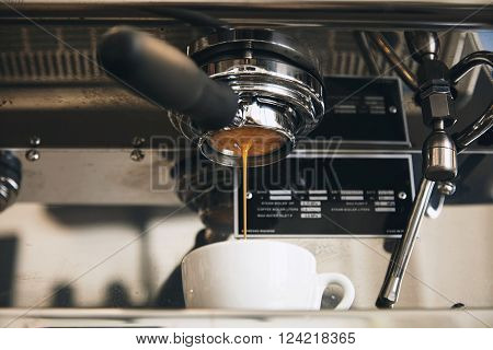 Fresh Espresso Coffee Brewing Through The Bottomless Portafilter In White Ceramic Cup In Artisan Caf