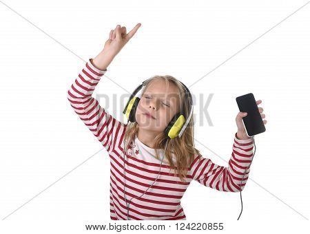 sweet little girl 7 years old with blonde hair and closed eyes listening to music with headphones and mobile phone singing and dancing happy