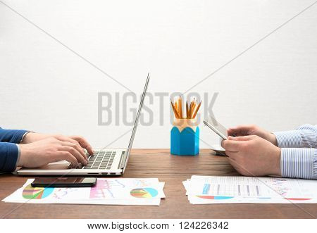 Businessman's at workplace use different devices at one table