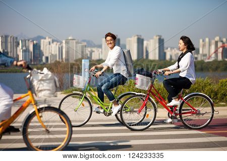 SEOUL KOREA - APRIL 24 2015: People cycling at a racreation park zone on the bank of Hangang river in Seoul Korea