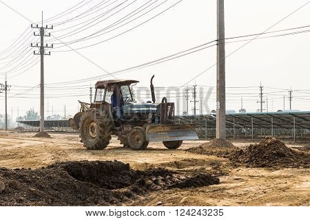 Petchaburi, Thailand - February 20, 2016: One worker drives wheel dozer in the under construction solar farm on February 20, 2016 in Petchaburi, Thailand