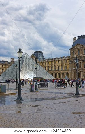 PARIS FRANCE - MAY 4 2012: Louvre Pyramid near Louvre Palace in Paris in France. Palace of Louvre now is a museum. Louvre Pyramid is a large metal and glass pyramid