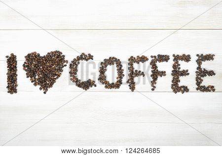 Top view of coffee beans spelled phrase I love coffee on light wooden surface. Concept.