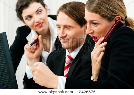 Small business team working in the office on their phones and computers in a shared project