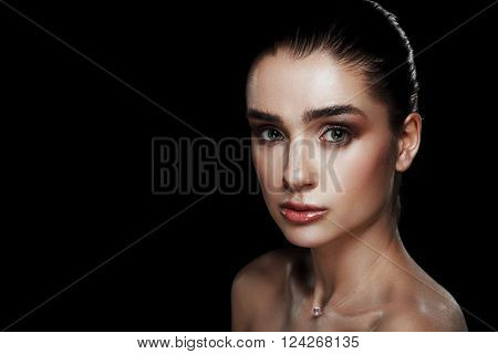 Beauty Portrait of Pretty Woman with Strobing Makeup. Wet Body Effect. Strobing or Highlighting makeup technique. Professional Retouch and Studio Photo. Ideal commercial concept. Black background