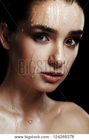 Beauty Portrait Of Young Woman With Strobing Makeup Liquid On Face. Wet Body Effect. Strobing Highli