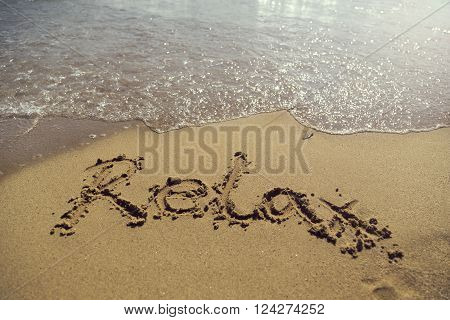 Word relax handwritten in golden sand on the beach next to the waterline