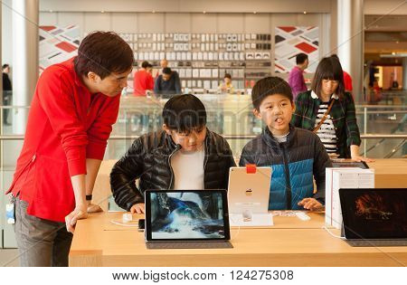 HONG KONG, CHINA - FEB 12: Unidentified boys talking about devices inside iStore with iPods and gadgets on February 12, 2016. Store sells Macintosh computers software iPod iPad other electronics
