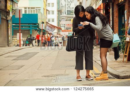 HONG KONG, CHINA - FEB 12: Two women watching cell phone to find way in big city on February 12, 2016. There are 1223 skyscrapers in Hong Kong.