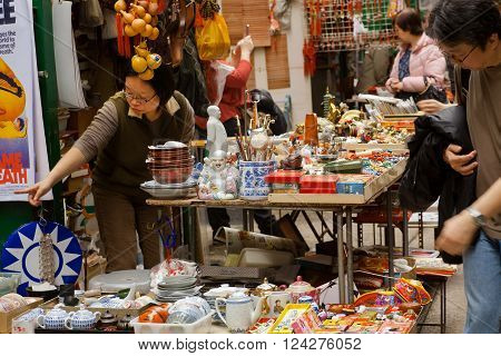 HONG KONG, CHINA - FEB 12: Antique market trader showing some crockery and old statues for customers on February 12, 2016. More than 47 million tourists visit Hong Kong annually