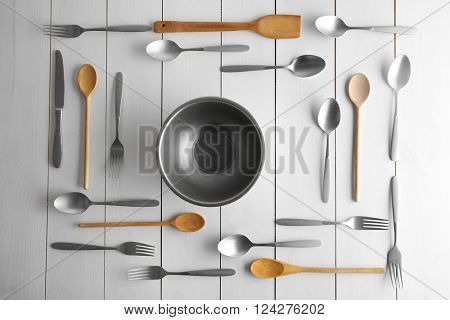 Bowl and flatware on white table, top view