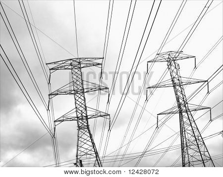View of tops of power line towers against a cloudy sky.